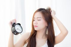 Beautiful asian young woman wake up in morning annoyed alarm clock holding hand. Stock Photos