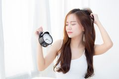 Beautiful asian young woman wake up in morning annoyed alarm clock holding hand. Stock Photo