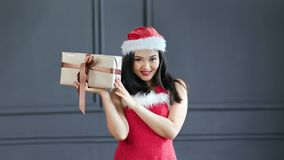 Beautiful Asian young woman wearing Santa Claus suit smiling and holding gift box at studio. Medium shot. Happy adorable Christmas female posing with big