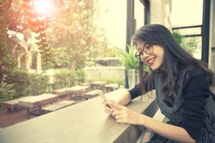 Beautiful asian younger woman laughing with happiness emotion re. Beautiful asian younger  woman laughing with happiness emotion reading smart phone Royalty Free Stock Photo