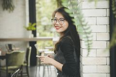 Beautiful asian younger woman toothy smiling face happiness emotion with smartphone in hand stock image
