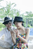 Beautiful asian younger woman toothy smiling face and playing on. Beautiful asian younger women toothy smiling face and playing on smart phone screen Royalty Free Stock Images