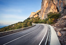 Beautiful asphalt road in autumn forest at sunrise. Mountains Royalty Free Stock Photography