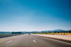 Beautiful asphalt road, freeway, motorway, highway under sunny b Royalty Free Stock Image