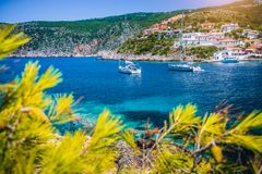 Beautiful Assos village, Kefalonia. Greece. White cruise yachts staying at anchor in beautiful emerald green colored. Lagoon water. Framed by pine trees branch stock images