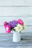 Beautiful asters in a vase on the boards stock photos