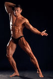 Beautiful athlete. Strong beautiful sportsman on the black backgroung Royalty Free Stock Photo