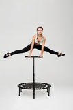 Beautiful athlete doing split jumping on rebounder holding handle Stock Image