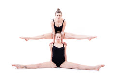 2 beautiful athlete flexible young women siting in split one on top of shoulders of another Royalty Free Stock Photo