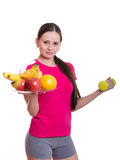 Beautiful athlete holding a plate of fruit and dumbbell Royalty Free Stock Photography