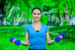 Beautiful, athlete involved in sports on the street, conducts training with dumbbells. Royalty Free Stock Image