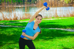 Beautiful, athlete involved in sports on the street, conducts training with dumbbells Stock Image