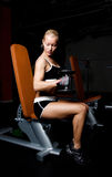 Beautiful athlete lifting heavy dumbbells. Portrait of a blond sportswoman lifting heavy dumbbells in empty dark gym room Royalty Free Stock Images