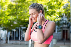 A beautiful athlete putting her headphones Stock Image