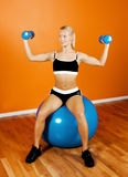 Beautiful athlete sitting on fitness ball Stock Image