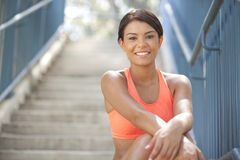 Beautiful Athlete smiling at camera. Beautiful young woman, in athletic wear sitting on steps Royalty Free Stock Photography