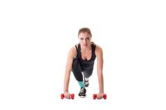 Beautiful athlete squatting with dumbbells Stock Image