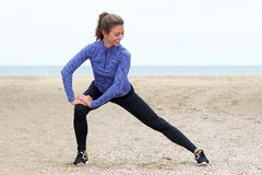 Beautiful athlete in stretch on beach Royalty Free Stock Photos
