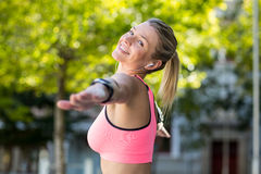A beautiful athlete stretching her arms Stock Photography