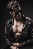 Beautiful athletic bodybuilder male model posing in studio. Expression on camera. Brutal man in leather suit. Athletic, male, model, brutal leather suit body Stock Photo