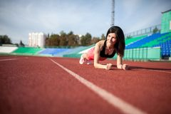 Beautiful and athletic brunette girl in in shorts and tank top push ups at the stadium.  royalty free stock photo