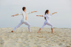 Beautiful, athletic couple in white clothes making yoga exercis. Healthy lifestyle concept. fitness, sport. beautiful, athletic couple in white clothes making royalty free stock images