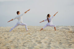 Beautiful, athletic couple in white clothes making yoga exercis royalty free stock image