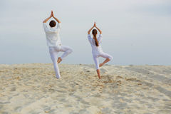 Beautiful, athletic couple in white clothes making yoga exercis. Healthy lifestyle concept. fitness, sport. beautiful, athletic couple in white clothes making royalty free stock photography