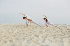 Beautiful, athletic couple in white clothes making yoga exercis. Healthy lifestyle concept. fitness, sport. beautiful, athletic couple in white clothes making Stock Photos