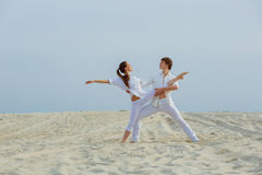 Beautiful athletic couple workout dance  on the beach. Fitness, sport, healthy and lifestyle concept Stock Image