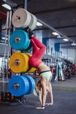 Girl in the gym and standing on his hands. Beautiful athletic fitness girl in sportswear standing on her hands upside down stock photo