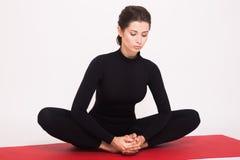 Beautiful athletic girl in black suit doing yoga asanas. Isolated on white background. stock photo
