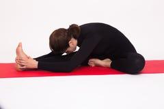 Beautiful athletic girl in black suit doing yoga asanas. Isolated on white background. royalty free stock photography