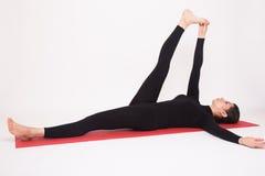 Beautiful athletic girl in black suit doing yoga asanas. Isolated on white background. royalty free stock images