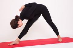 Beautiful athletic girl in black suit doing yoga asanas. Isolated on white background. stock photos