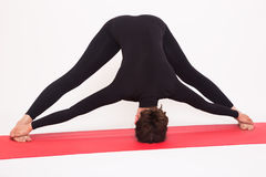 Beautiful athletic girl in black suit doing yoga asanas.  on white background. Royalty Free Stock Images