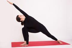 Beautiful athletic girl in black suit doing yoga asanas.  on white background. Royalty Free Stock Image