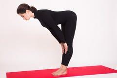 Beautiful athletic girl in black suit doing yoga asanas.  on white background. Royalty Free Stock Photo