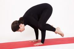 Beautiful athletic girl in black suit doing yoga. Kakasana asana - crow pose. Isolated on white background. Stock Photography