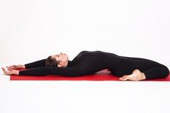 Beautiful athletic girl in a black suit doing yoga. Supta Virasana asana lightning sleeping pose. Isolated on white background. Stock Photography