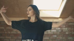 Beautiful athletic girl dancing vogue and jumping closeup. Beautiful athletic girl in black dancing vogue or hip hop and jumping. Woman throws hair up. closeup stock footage