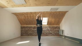 Beautiful athletic girl dancing vogue and jumping long shot. Beautiful athletic girl in black dancing vogue or hip hop and jumping on brown background. Long shot stock footage