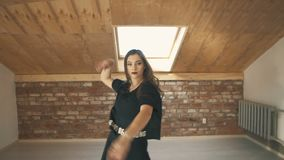 Beautiful athletic girl dancing vogue and jumping Mid shot. Beautiful athletic girl in black dancing vogue or hip hop and jumping. Mid shot stock video footage