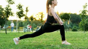 Beautiful athletic girl doing fitness and stretching exercises, training in park at sunset. Healthy and sporty lifestyle concept, people walking on background stock footage