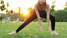 Beautiful athletic girl doing fitness and stretching exercises, training in park at sunset. Healthy and sporty lifestyle concept, people walking on background stock video
