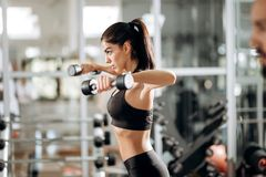 Beautiful athletic girl dressed in black sports top and tights builds up muscles with dumbbells in the gym royalty free stock photo