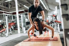 Beautiful athletic girl dressed in black sports top and tights is doing plank and the coach corrects her in the gym royalty free stock photos