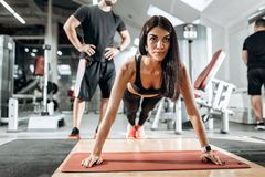 Beautiful athletic girl dressed in black sports top and tights is doing plank under the supervision of a coach in the stock photos