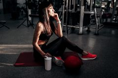 Beautiful athletic girl dressed in black sports top and tights is sitting on the fitness mat in the gym royalty free stock photos