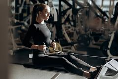 The beautiful athletic girl dressed dressed in a black sportswear is doing sport exercises with equipment on the bench stock photos